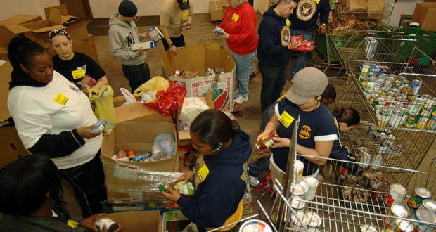 U.S Navy sailors check canned foods at a food bank