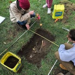 "This image shows two students over a small ""grave"" that they excavated for their class ANTHROP5686. They are planning the location of several pieces of evidence, including plaster casts of bones."