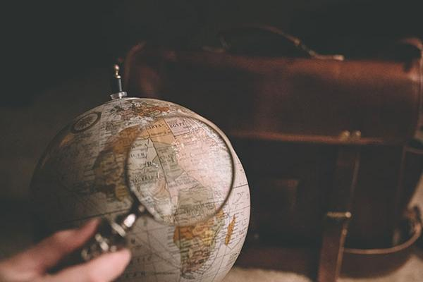 A photo of a magnifying glass, globe, and bag