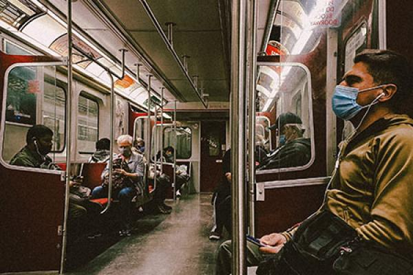 A photo of people riding public transportation during the COVID-19 pandemic
