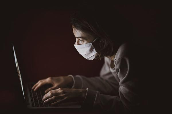 A photo of a woman wearing a surgical mask working on a laptop computer